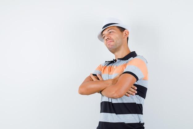 Tシャツと帽子で腕を組んで目をそらし、希望に満ちた若い男