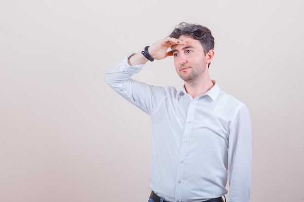 Young man looking away with hand over head in white shirt and looking pensive