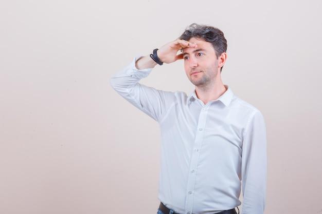 Молодой человек смотрит в сторону с рукой над головой в белой рубашке и смотрит задумчиво