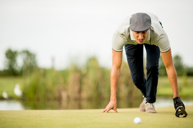 Young man looking at ball while crouching on golf course
