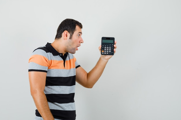 Young man looking at calculator in t-shirt and looking surprised .