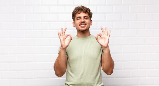 集中して瞑想しているように見え、満足してリラックスしていると感じ、考えたり選択したりする若い男