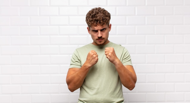 Young man looking confident, angry, strong and aggressive, with fists ready to fight in boxing position