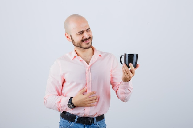Young man looking at cup in pink shirt,jeans and looking optimistic. front view.
