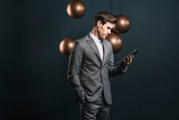 Young man looking at digital tablet standing in front of streamlined mirror round copper chandelier
