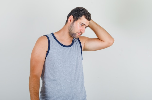 Young man looking down while holding head in grey singlet and looking exhausted