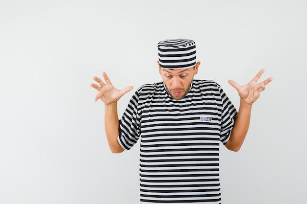 스트라이프 티셔츠 모자에 제기 손으로 내려다보고 놀란 젊은 남자