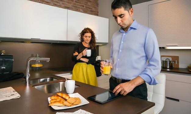 仕事に行く前に家で速いコーヒーを飲んでいる巻き毛の女性の間に電子タブレットを探している若い男