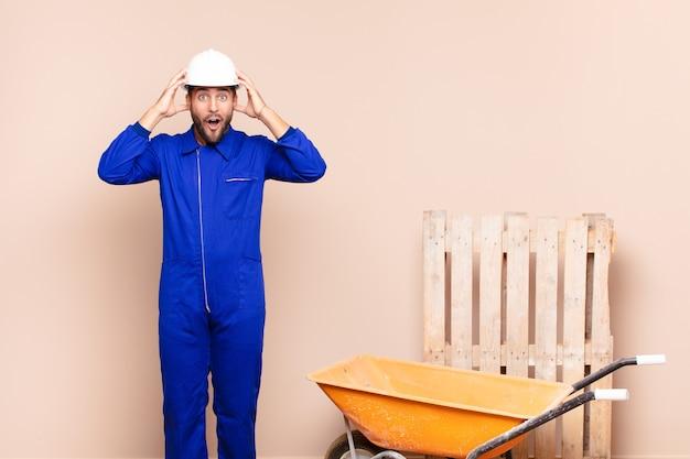 Молодой человек выглядит взволнованным и удивленным, с открытым ртом и обеими руками за голову, чувствуя себя счастливым победителем в концепции строительства