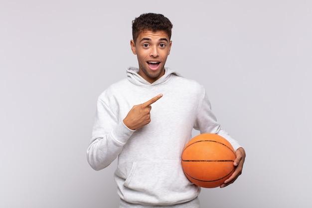 スペースをコピーするために横と上を指して興奮して驚いたように見える若い男。バスケットコンセプト