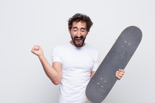 Молодой человек выглядит очень счастливым и удивленным, празднует успех, кричит и прыгает