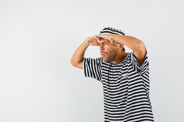 스트라이프 티셔츠 모자에 머리 위로 손으로 멀리보고 놀란 젊은 남자
