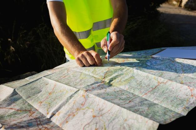 紙の地図で場所を探している若い男