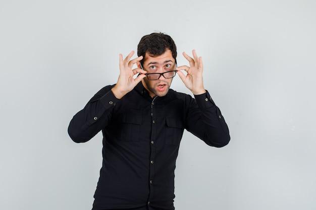 Giovane che osserva sopra gli occhiali in camicia nera e sembra curioso.
