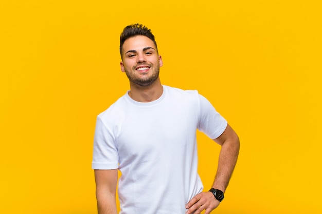 Young  man looking happy, cheerful and confident, smiling proudly and looking to side with both hands on hips against orange wall