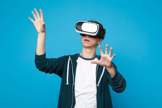 Young man looking on headset touch something like push click on button, pointing at floating virtual screen isolated on blue wall . people sincere emotions, lifestyle concept.
