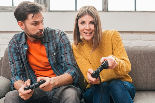Young man looking at her girlfriend playing the video game with joystick