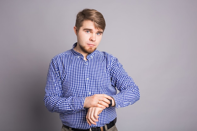灰色の壁越しに彼の腕時計を見ている若い男。