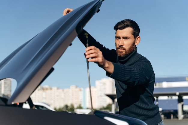 Young man looking under the hood of breakdown car. car breakdown. concentrated young man try to repair the engine, looking inside it while standing outdoors