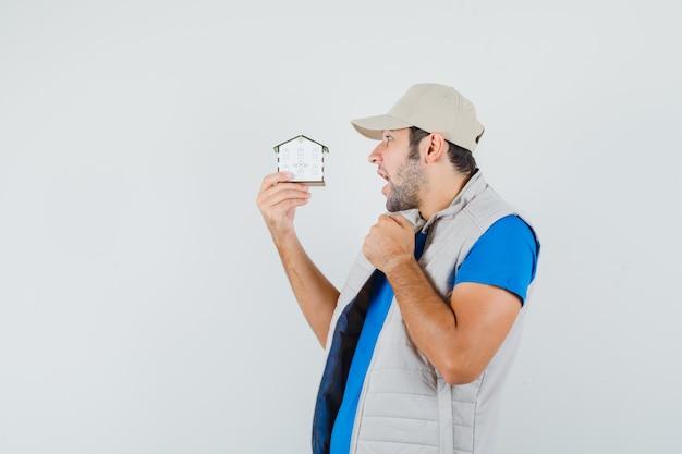 Giovane che guarda il modello di casa in t-shirt, giacca, berretto e guardando stupito, vista frontale.
