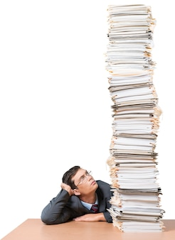 Young man looking on huge stack of papers, isolated on white background