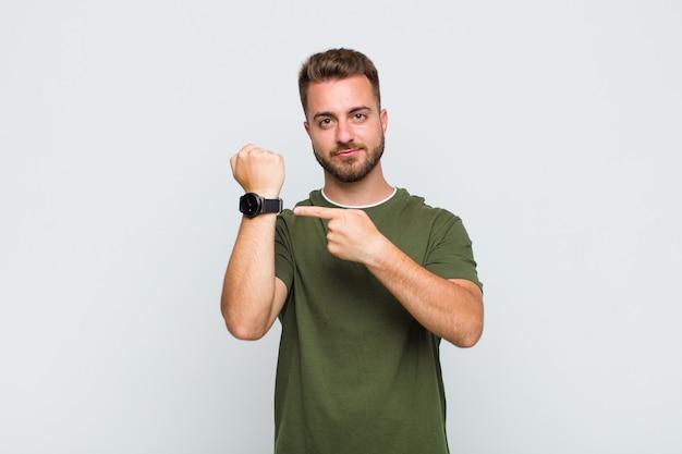 Молодой человек выглядит нетерпеливым и сердитым, указывая на часы, прося пунктуальности, хочет прийти вовремя
