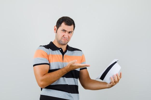 Giovane che osserva all'interno del cappello in maglietta, cappello e che sembra arrabbiato