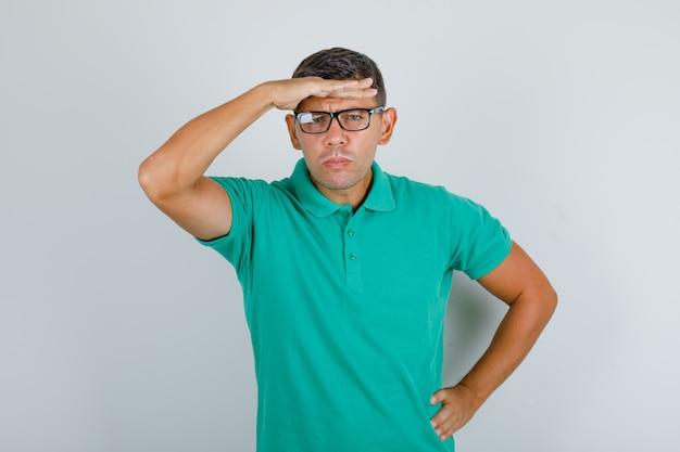 緑のtシャツ、メガネで目の上に手を置くことによってカメラに探している若い男。