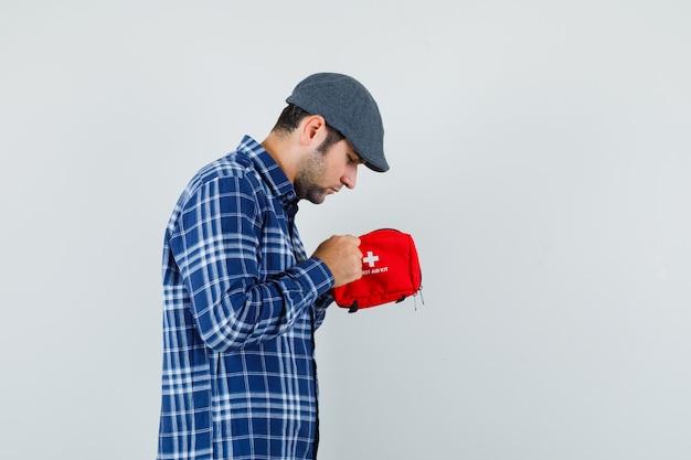 Giovane che esamina kit di pronto soccorso in camicia, berretto e sembra curioso .