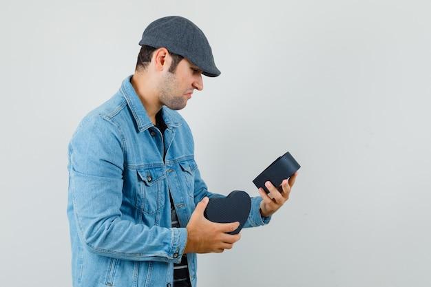 ジャケット、キャップ、動揺してギフトボックスを探している若い男。