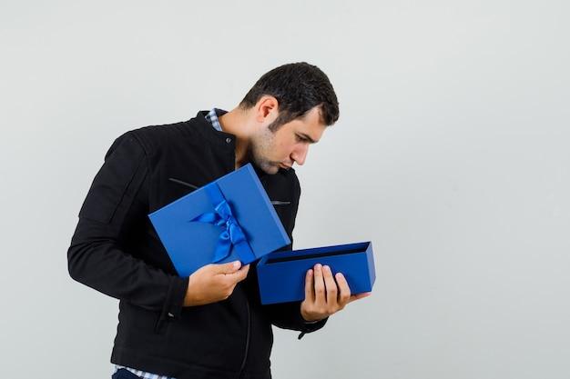 シャツ、ジャケットのプレゼントボックスを見て、好奇心旺盛な青年。