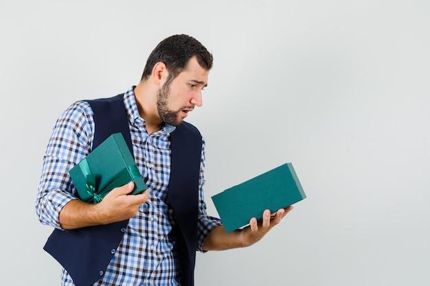 シャツ、ベスト、ダウンキャスト、正面図で現在のボックスを探している若い男。