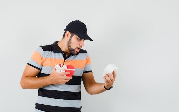 Tシャツ、キャップ、ショックを受けた、正面図でプレゼントボックスを探している若い男。