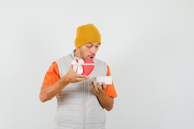 Tシャツ、ジャケット、帽子でプレゼントボックスを見て、驚いて、正面図を探している若い男。