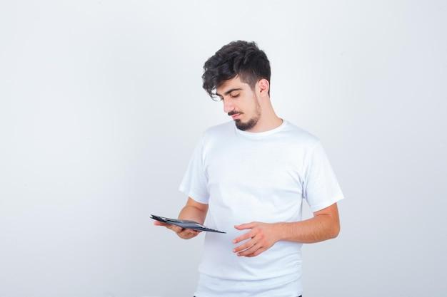 白いtシャツで財布を見て物思いにふける若い男