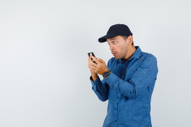 Giovane che guarda il cellulare in camicia blu, berretto e sembra scioccato. vista frontale.