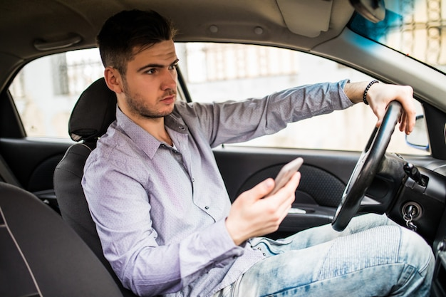 Young man looking at mobile phone while driving a car.