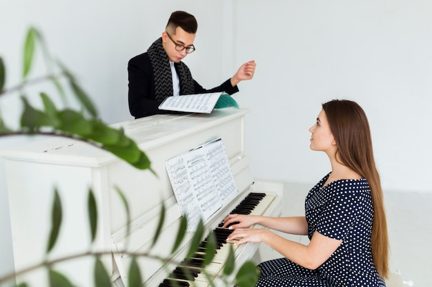 Young man looking at musical sheet assisting the woman playing piano