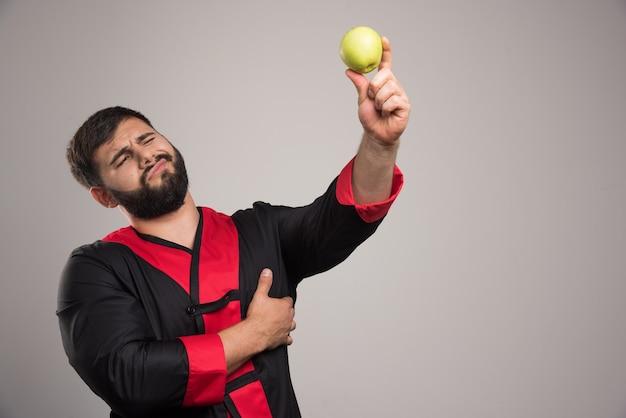 暗い壁にリンゴを見ている若い男。