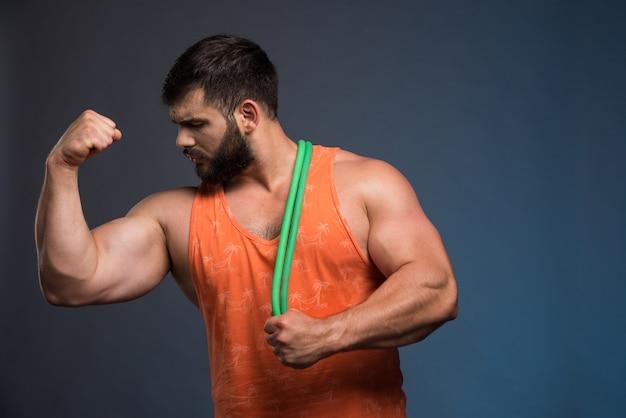 Молодой человек смотрит на его мышцы и держит резину для спорта.