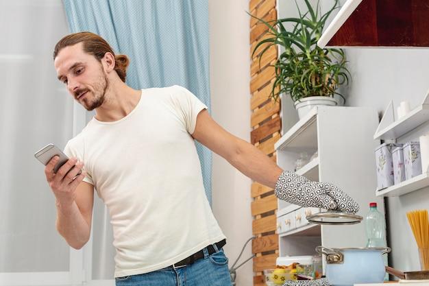 Молодой человек смотрит на телефон и держит крышку горшка