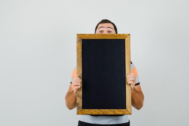 Tシャツの黒いフレームを見て、テキストの隠されたスペースを探している若い男