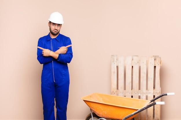 의아해하고 혼란스럽고 안전하지 않고 의심스러운 건설 개념으로 반대 방향으로 가리키는 젊은 남자
