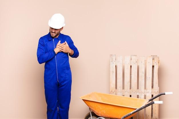 Молодой человек выглядит грустным, обиженным и убитым горем, держит обе руки близко к сердцу, плачет и чувствует себя подавленным концепция строительства