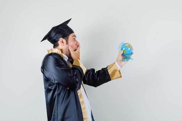 Giovane che guarda il globo della scuola in uniforme laureato e che sembra sorpreso.