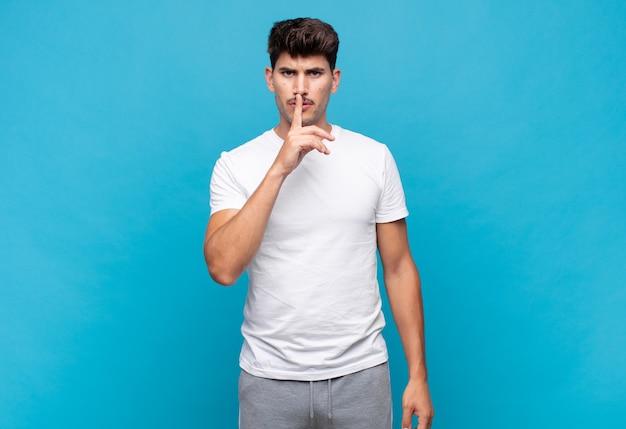 Молодой человек выглядит серьезным и скрещенным, прижимая палец к губам, требуя тишины или тишины, сохраняя секрет