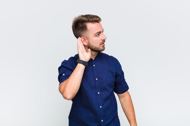 Молодой человек выглядит серьезным и любопытным, слушает, пытается услышать секретный разговор или сплетню, подслушивает
