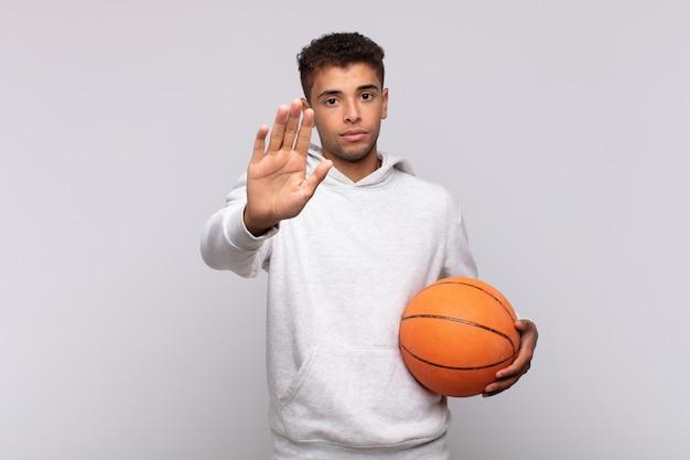 真面目で、厳しく、不機嫌で、怒っているように見える若い男は、手のひらを開いて停止ジェスチャーを示しています。バスケットコンセプト