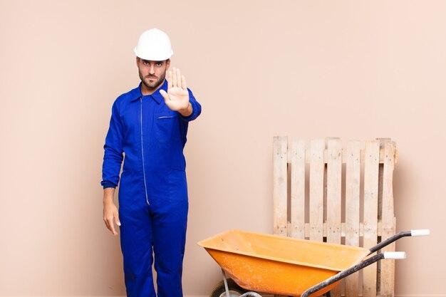심각한, 선미, 불쾌 하 고 화가 보여주는 오픈 손바닥 만들기 중지 제스처 건설 개념을 찾고 젊은 남자