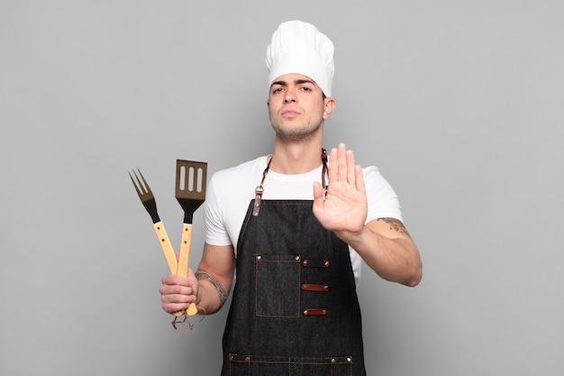 真面目で、厳しく、不機嫌で、怒っているように見える若い男は、手のひらを開いて停止ジェスチャーを示しています
